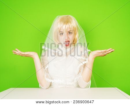 Beautiful Bride In A Wedding Dress Keeps Hands Like Scales. The Girl In Doubt Makes An Imaginary Cho