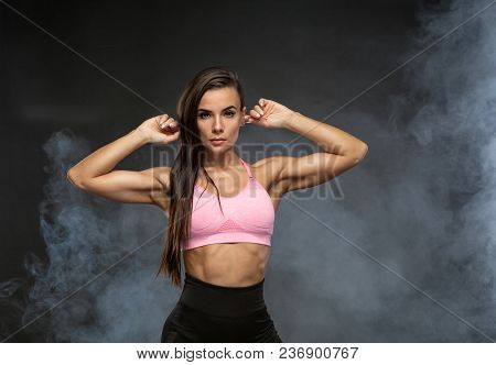 Image Of Fitness Woman In Sports Clothing In The Smoke. Young Female Model With Muscular Body. Horiz