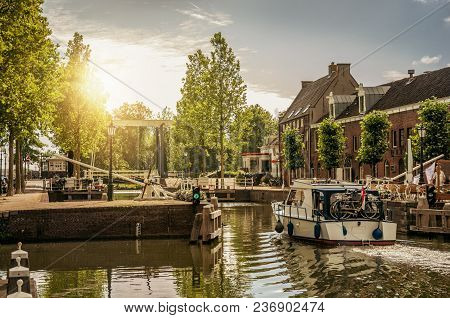 Boat Passing By A Tree-lined Narrow Canal In The Sunrise At Weesp. Quiet And Pleasant Village Full O