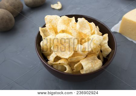 Potato Chips With Cheese In A Plate That Is Located On A Gray Background.