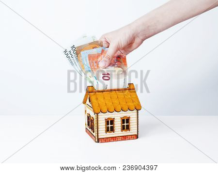 A Female Hand Putting A Set Of Euro Into A Money Box In The Form Of A Wooden House. The Concept Of F