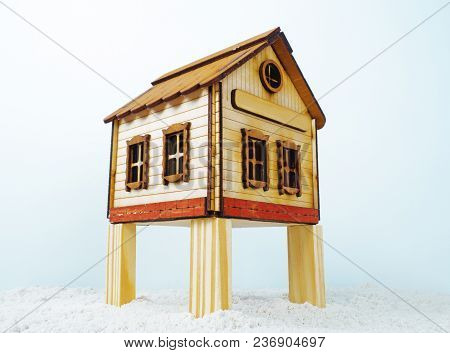 Model Traditional Wooden House On Stilts. Wooden House Toy On The Sand, Snow. Isolated Wooden Toy Ho