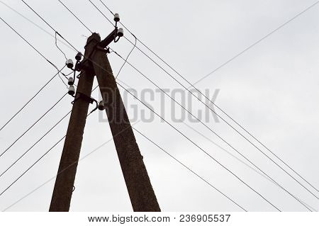Electric Concrete Pillar Of High Voltage Power Line With Wires Against The Sky.