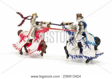 Joust Of Toy Medieval Knights. Isolated On White Background. Toy Horse Knights Tournament