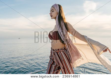 A Luxurious Young Girl In Stylish Summer Clothes Posing On Her Yacht, Enjoying The Sun And Warm Wind