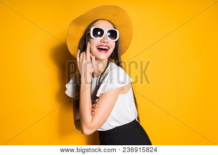 Happy Smiling Girl In Fashion Hat And Sunglasses Posing On Orange Background