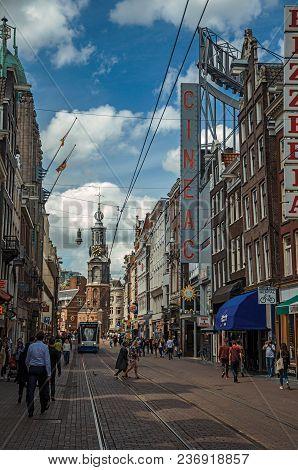Amsterdam, Northern Netherlands - June 26, 2017. Street With Brick Buildings, Steeple, Tram And Peop