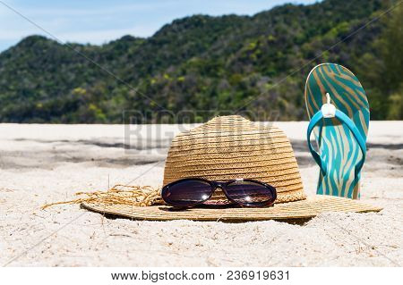 Straw Hat, Sunglasses And Flip Flops On A Tropical Beach. Summer Vacation Concept.