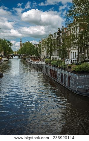 Tree-lined Canal With Old Brick Buildings, Steeple, Moored Boats And Cloudy Blue Sky In Amsterdam. T