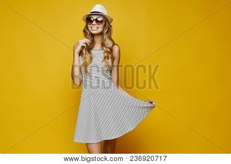 Beautiful Sexy And Fashionable Blonde Model Girl, In White Stripe Dress And Hat And Sunglasses, Hold