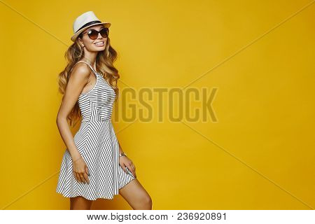 Cheerful And Smiling Blonde Model Sexy Girl With Perfect Body, In White Striped Fitting Dress, Hat A