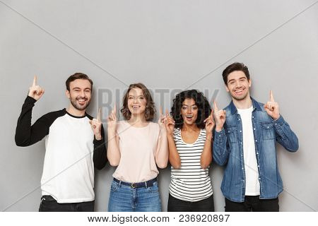 Image of happy group of friends standing isolated over grey wall background looking camera pointing.
