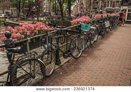 Amsterdam, Northern Netherlands - June 26, 2017. Bridge Over Canal With Flowers, Bicycles, Old Build