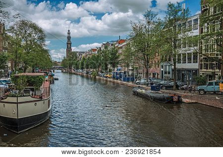 Tree-lined Canal With Old Brick Buildings, Steeple, Moored Boats And Sunny Blue Sky In Amsterdam. Th