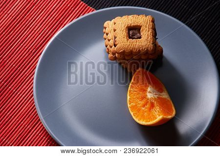 Chocolate Chip Cookies And Orange On Gray Plate And On Red With Black Table