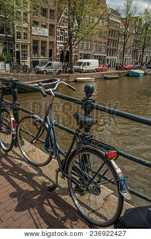 Amsterdam, Northern Netherlands - June 26, 2017. Bridge On Canal With Iron Balustrade, Bicycle, Old