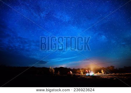 Camping Fire Under The Amazing Blue Starry Sky With A Lot Of Shining Stars And Clouds. Travel Recrea