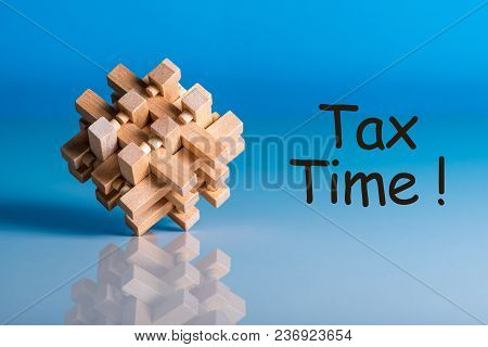 Tax Time - Message On Blue Background With Wooden Brain Teaser.