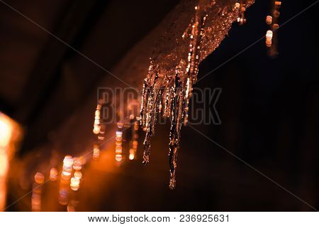 Icicles Illuminated By Warm Street Light In The Night Against Dark Sky.
