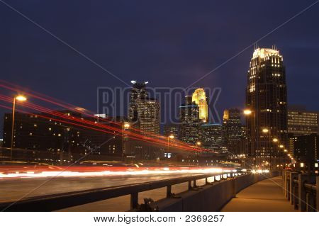 Minneapolis City Skyline At Dusk With Bridge And Moving Cars