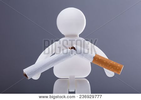 Human Figure With Broken Cigarette On Grey Background
