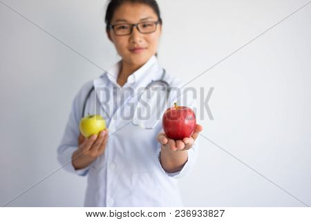 Content Young Asian Female Doctor Offering Red Apple. Healthy Nutrition Concept. Isolated Front Clos