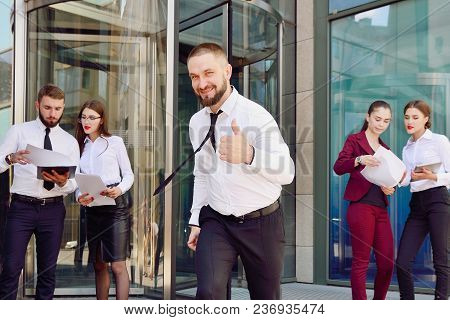 A Young Male Businessman Is Enjoying A Successful Deal On The Background Of Office Workers. Demonstr