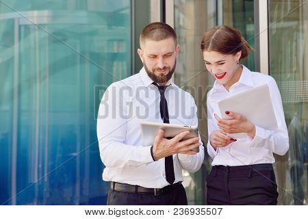 Young Man And Girl In White Shirts With A Tablet On The Background Of An Office Building. Office Wor