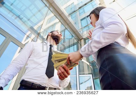A Girl Gives A Man In The Hands Of Money In The Background Of An Office Building. Payment For Servic