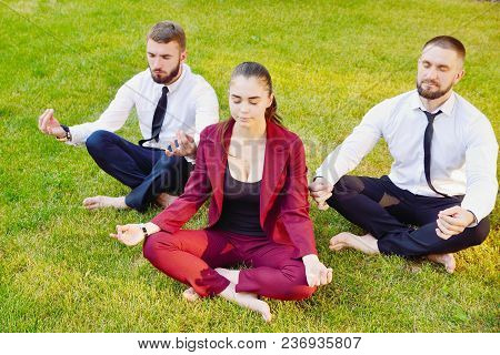 Office Yoga. Three Young Employees In A Lotus Pose Are Sitting On Green Grass And Meditate. Recreati