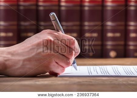 Human Hand Signing Document Over Wooden Desk