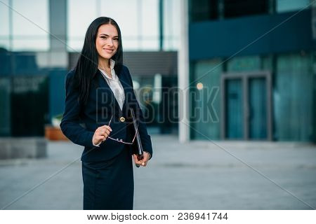Smiling businesswoman poses against business center. Modern financial building, cityscape. Successful female businessperson