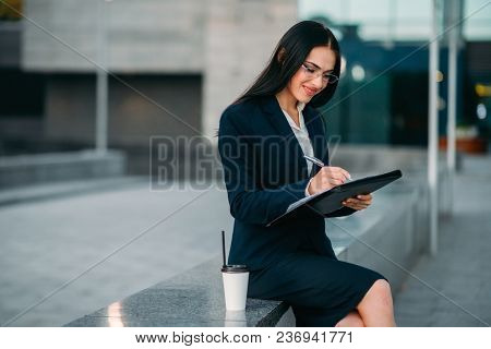 Businesswoman in suit writing in notebook outdoor, business center on background. Modern financial building, cityscape. Successful female businessperson