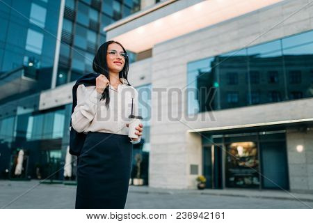 Business woman in glasses, suit and coffee in hand. Modern building, financial center, cityscape. Successful female businessperson