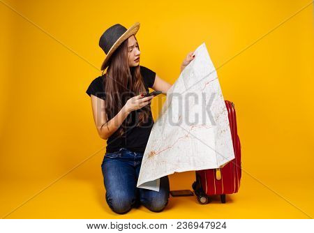 A Young Girl In A Hat Went On A Trip With A Large Red Suitcase, Studies A Map Of The City