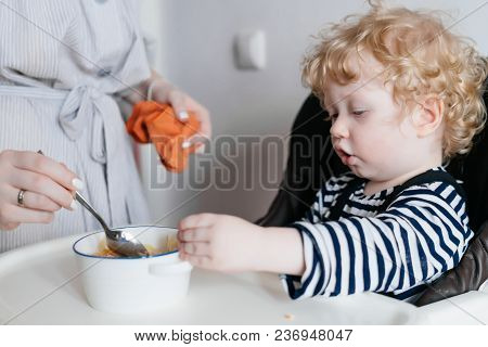 Family Dinner, A Caring Young Mother Feeds Her Little Curly Son With Useful Porridge