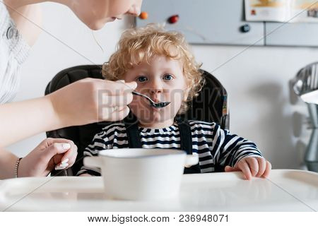 Family Dinner, A Caring Young Mother Feeds Her Little Curly Son With Useful Porridge, In The Kitchen
