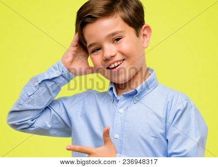Handsome toddler child with green eyes pointing away side with finger over yellow background