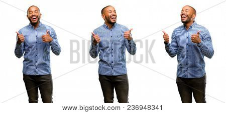 African american man with beard smiling broadly showing thumbs up gesture to camera, expression of like and approval