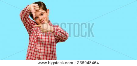 Handsome toddler child with green eyes confident and happy showing hands to camera, composing and framing gesture over blue background