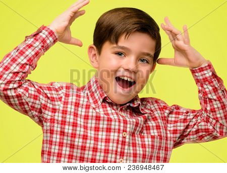 Handsome toddler child with green eyes happy and surprised cheering expressing wow gesture over yellow background