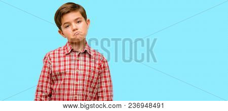 Handsome toddler child with green eyes having skeptical and dissatisfied look expressing Distrust, skepticism and doubt over blue background