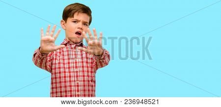 Handsome toddler child with green eyes disgusted and angry, keeping hands in stop gesture, as a defense, shouting over blue background