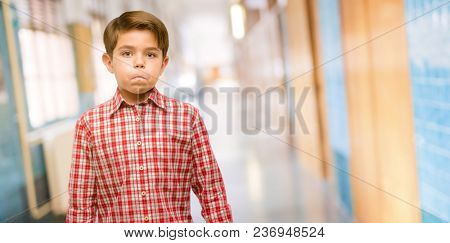 Handsome toddler child with green eyes puffing out cheeks, having fun making funny face at school corridor