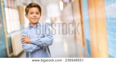 Handsome toddler child with green eyes with crossed arms confident and happy with a big natural smile laughing at school corridor