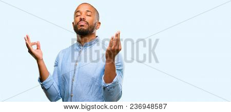 African american man with beard doing ok sign gesture with both hands expressing meditation and relaxation isolated over blue background