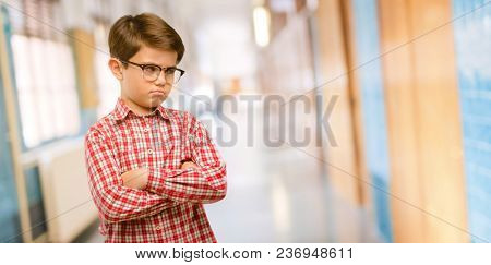 Handsome toddler child with green eyes irritated and angry expressing negative emotion, annoyed with someone at school corridor