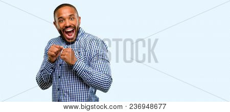 African american man with beard happy and surprised cheering expressing wow gesture isolated over blue background