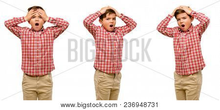 Handsome toddler child with green eyes stressful keeping hands on head, terrified in panic, shouting