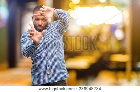 African american man with beard confident and happy showing hands to camera, composing and framing gesture at night